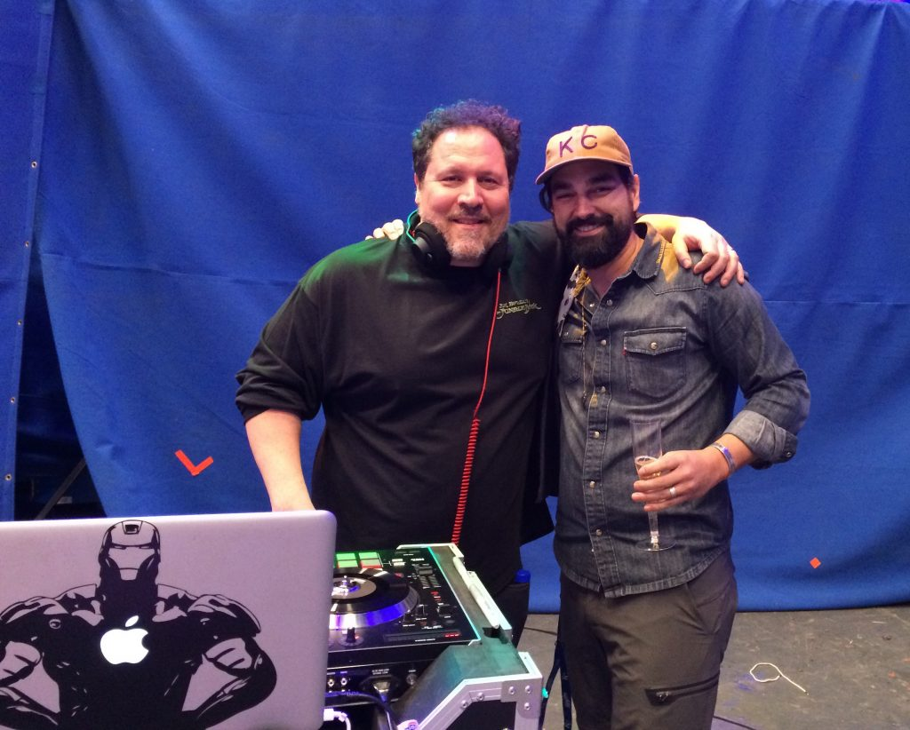 A photo of Barry wearing a KC baseball cap and holding a glass of champagne, with his arm around actor and filmmaker Jon Favreau, who he worked with on The Jungle Book