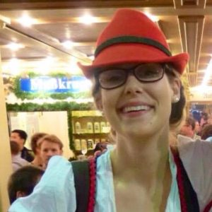 Selfie of Anna in a busy market. Anna's wearing a red fedora hat, glasses and a white shirt