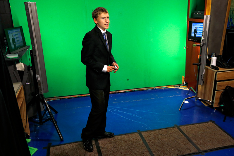 Carson, wearing a suit and tie, stands in front of a green screen