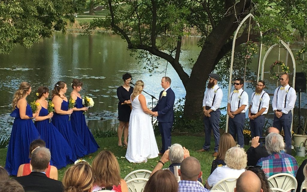 Sydney getting married at the edge of Potter Lake. There are four bridesmaids to the left wearing dark blue dresses and holding yellow flowers. There are four groomsmen to the right, wearing white shirts and great trousers. Guests watch on.