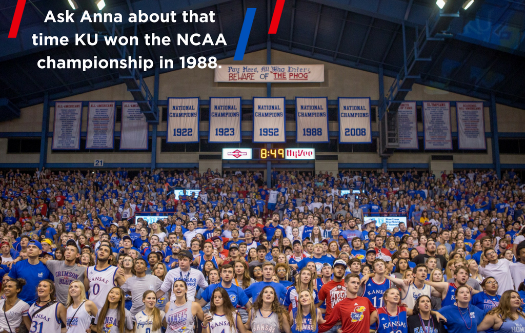 "Image of the inside of Allen Fieldhouse with a crowd singing and swaying. Banners display the five years KU has won the NCAA championship. Text reads ""Ask Anna about that time KU won the NCAA championship in 1988."