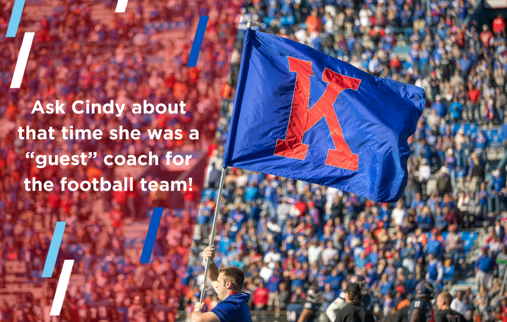 Image of a KU football game crowd, with a large blue flag with a K in the middle. Text reads, Ask Cynthia about that time she was a guest coach for the football team!